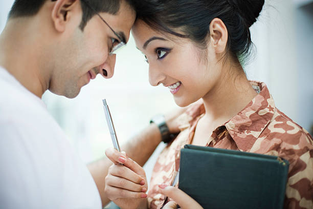 Romantic business woman and man touching forehead with each other. Indoor close-up shoot of a happy romantic business woman and man touching their forehead with each other and looking at each other's eyes with love. The young woman is holding a book and pointing a pen towards the young man, She is in a military patterned shirt, and her boyfriend is in white t-shirt. Horizontal, waist up composition with selective focus. romance stock pictures, royalty-free photos & images