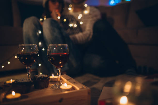 Romantic Christmas evening Young couple sitting on the floor enjoying the Christmas night date night romance stock pictures, royalty-free photos & images