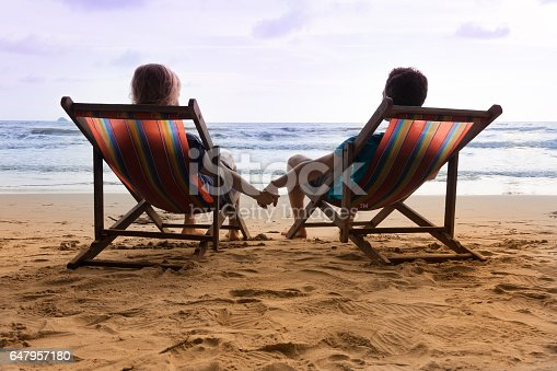 577645320 istock photo Romantic couple are sitting in deck chairs and holding their hands. 647957180