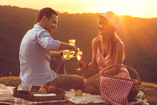 romantic couple at sunset enjoying with glass of wine. - romantisches picknick stock-fotos und bilder