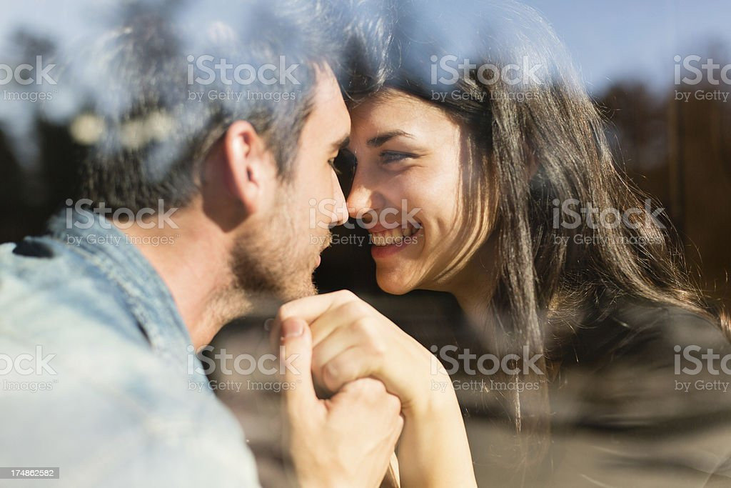 Romantic couple behind glass window stock photo