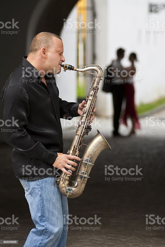 Romantic Couple Being Serenaded by Jazz Saxophone Musician royalty-free stock photo