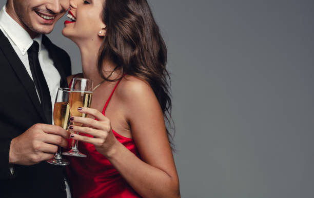 Romantic couple celebrating with champagne Close up of man and woman toasting champagne glasses. Romantic couple having drinks on grey background. evening wear stock pictures, royalty-free photos & images
