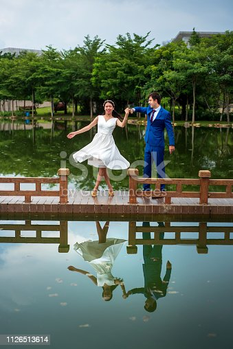 Romantic couple dancing by the lake reflected in the water