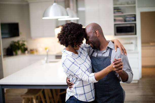Romantic couple dancing in kitchen Romantic couple dancing in kitchen at home 30 39 years stock pictures, royalty-free photos & images