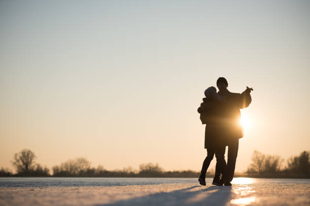 Romantic couple dancing on frozen lake stock photo