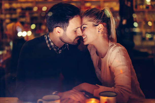 romantic couple dating in pub at night - calendar date stock photos and pictures