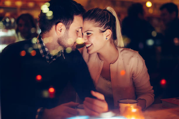 Romantic couple dating in pub at night stock photo