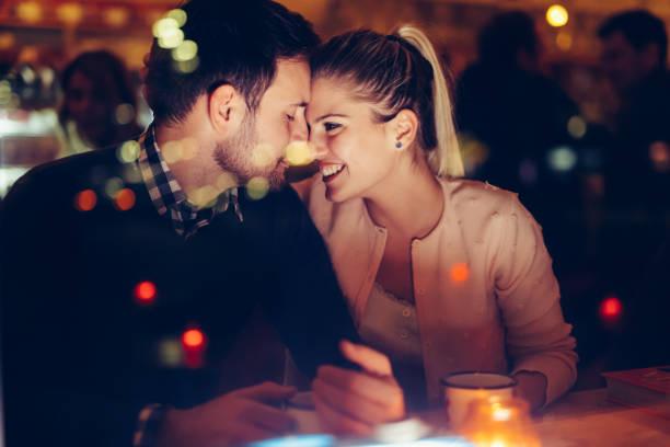 pareja romántica dating en pub por la noche - cena romantica fotografías e imágenes de stock