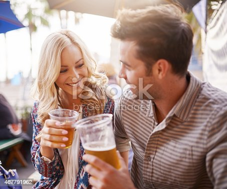 istock romantic couple drinking beer in plastic cups at outdoor bar 467791962