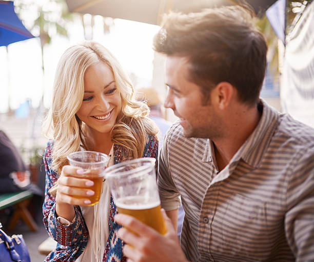 romantic couple drinking beer in plastic cups at outdoor bar stock photo