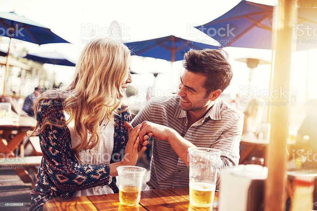 romantic couple drinking beer with artistic lens flare stock photo