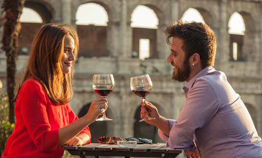 Romantic couple drinking glass of red wine sitting at restaurant table in front of colosseum in rome at sunset