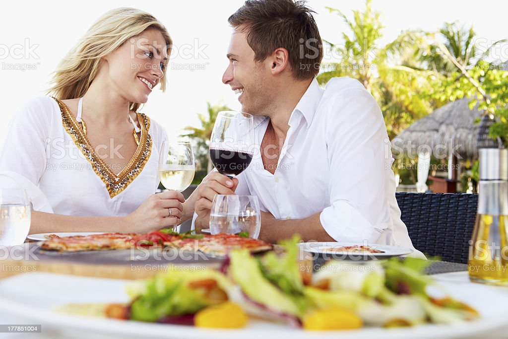 Romantic couple eating at outdoor restaurant stock photo