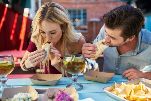 pareja romántica comer tacos callejeros en el restaurante al aire libre - comida mexicana fotografías e imágenes de stock