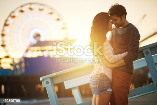 istock romantic couple embracing  at sunset 450395799