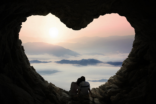 Romantic couple enjoy mountain view in cave