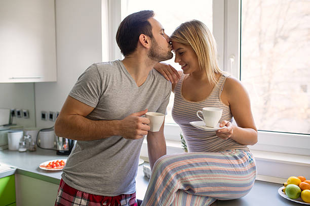 romantic couple enjoying coffee and romance on weekend morning. - couple lap stock photos and pictures
