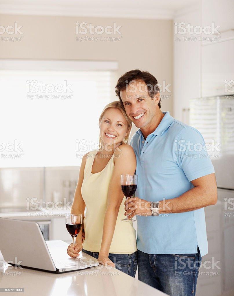Romantic couple enjoying drinks in kitchen royalty-free stock photo