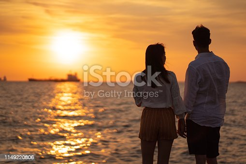 Young couple is standing by the sea and looking amazing sunset.