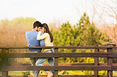 Romantic young couple enjoying time together outdoors, standing on the wooden bridge, embracing.