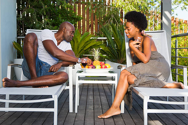 romantic couple enjoying wine and fruit on a deck - carolinemaryan stock pictures, royalty-free photos & images