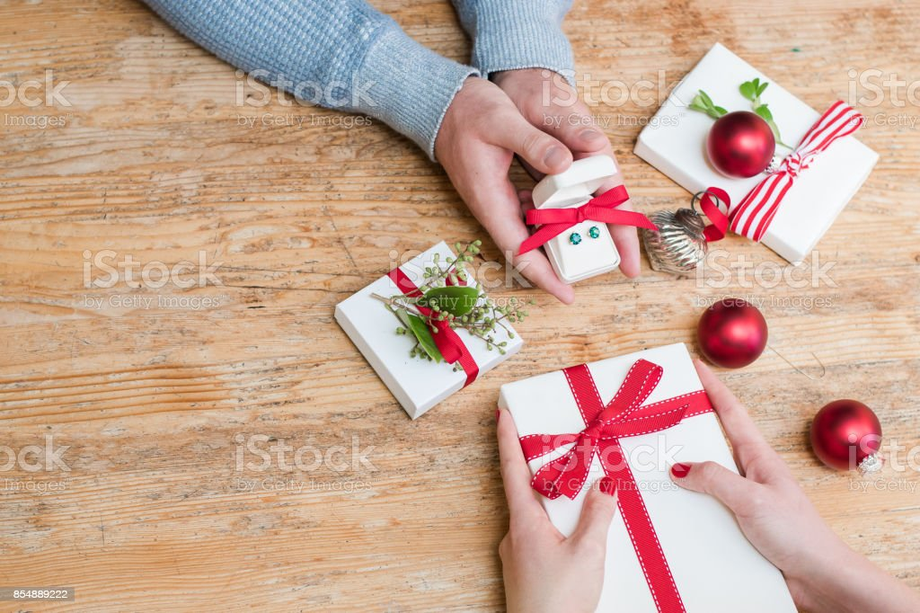 Romantic couple exchanges holiday Christmas gifts on a wooden table...