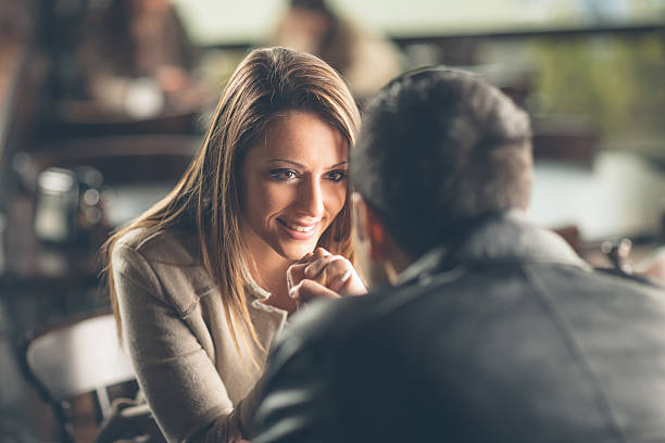 Romantic couple flirting at the bar Romantic young couple dating and flirting at the bar, staring at each other's eyes charming stock pictures, royalty-free photos & images