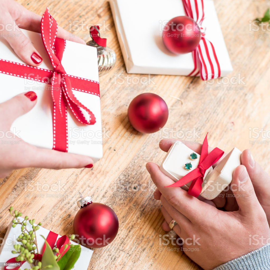 Romantic couple gives holiday Christmas gifts with red bows and...