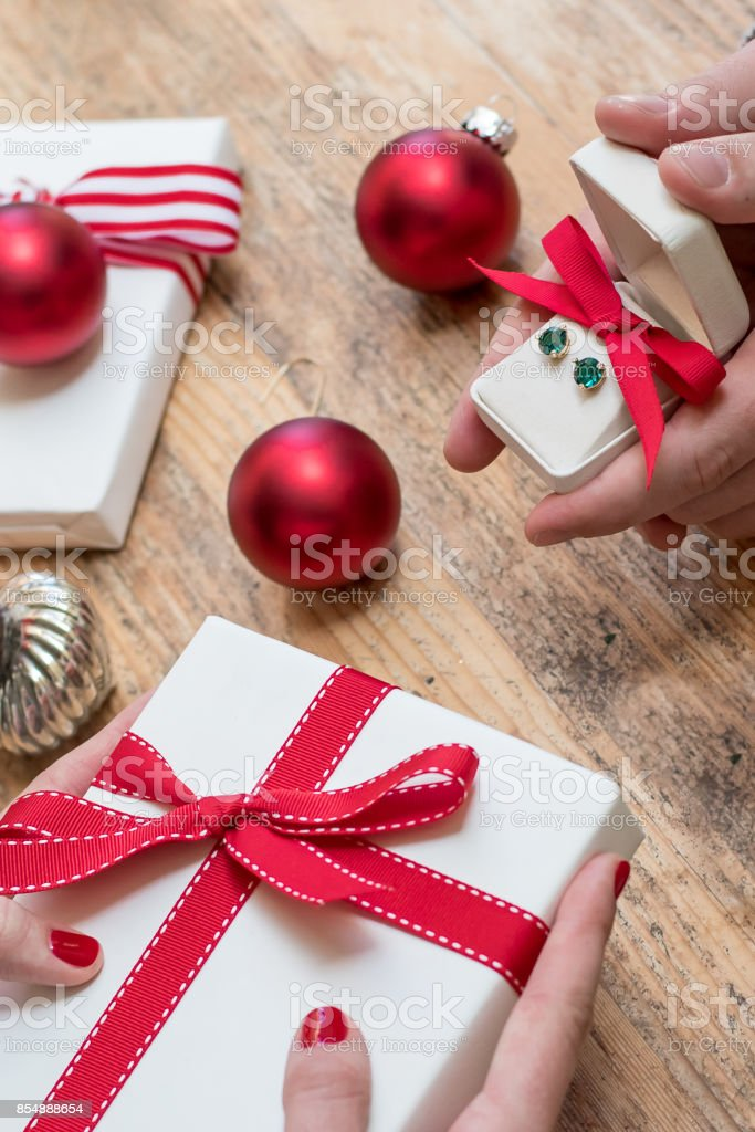 Romantic Couple Gives Holiday Christmas Gifts With Red Bows And Christmas Deocorations On A Wooden Table