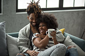 Young couple on bed enjoy in weekend, they smiling and drinking coffee