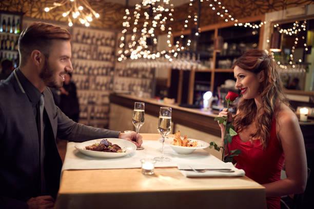 romántica pareja cenar en restaurante - cena romantica fotografías e imágenes de stock