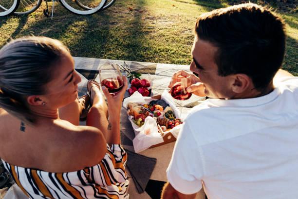 romantisch zu zweit mit einem picknick bei sonnenuntergang - romantisches picknick stock-fotos und bilder