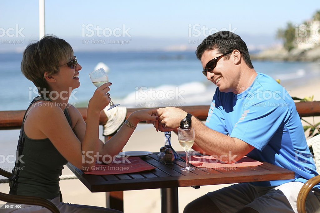 Romantic couple having drinks on the boardwalk royalty-free stock photo