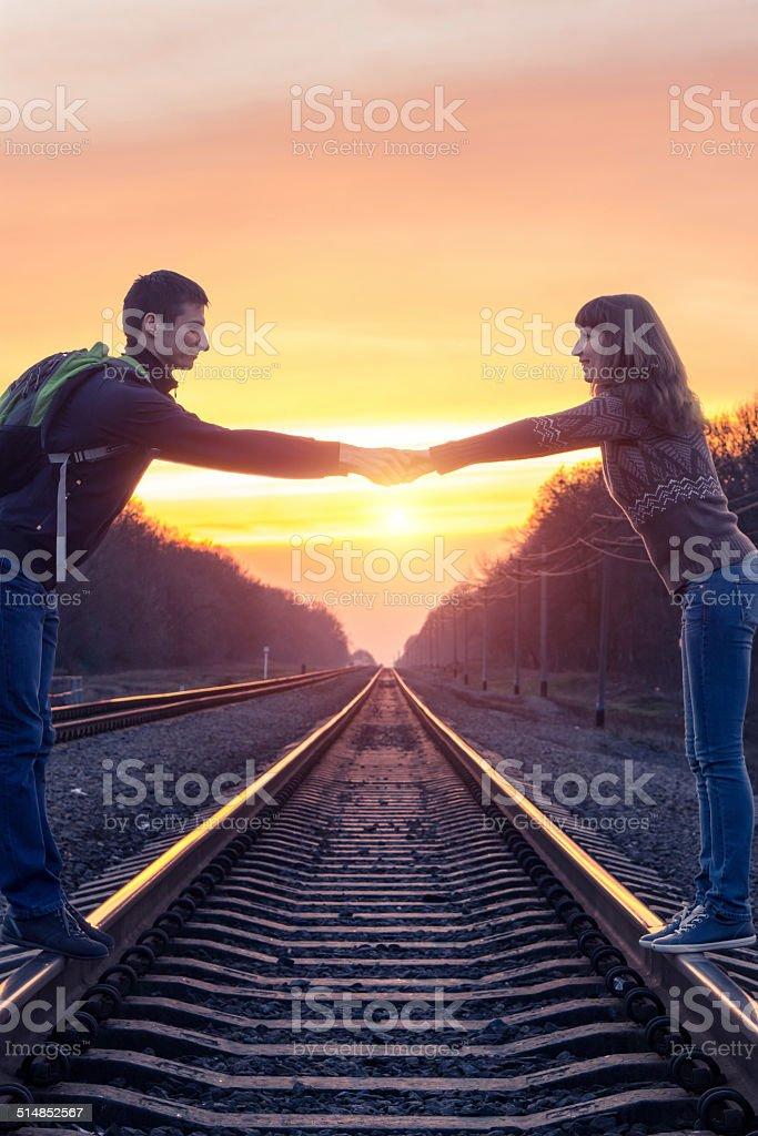 Romantic couple holding at sunset on railroad stock photo
