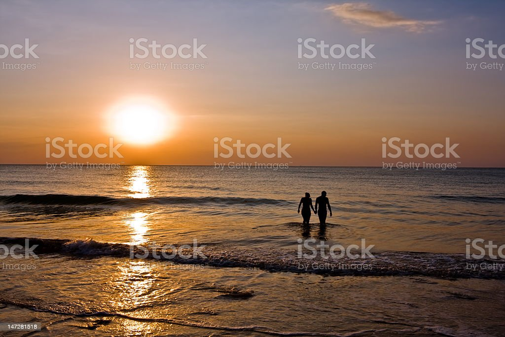 romantic couple holding hands in the ocean stock photo