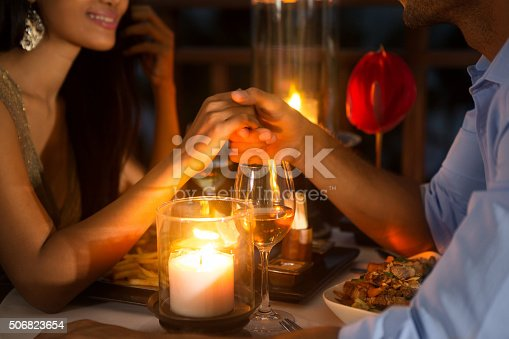 istock Romantic couple holding hands together over candlelight 506823654