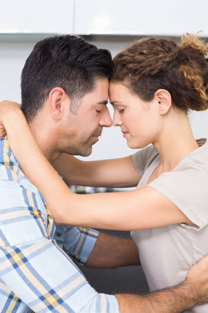 romantisches paar umarmt mit augen geschlossen - geschlossene küchen stock-fotos und bilder