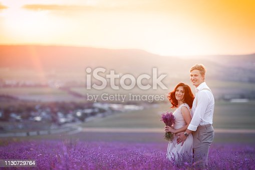 istock Romantic couple in an endless lavender field at sunset. blond Man and red-haired girl with a bouquet of flowers in love and hugs. French lavender fields 1130729764