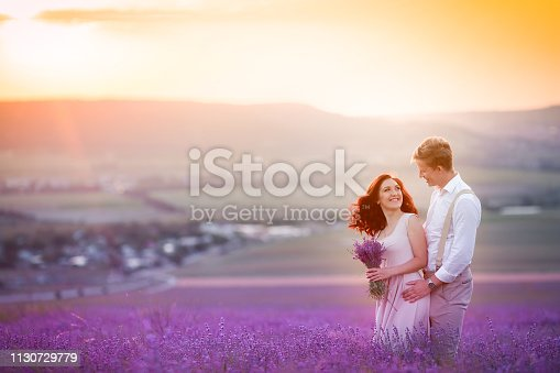 istock Romantic couple in an endless lavender field at sunset. blond Man and red-haired girl with a bouquet of flowers in love and hugs. French lavender fields 1130729779