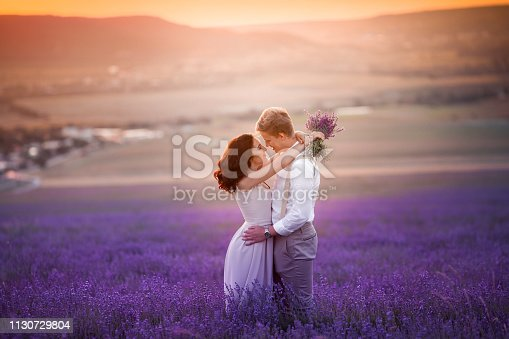istock Romantic couple in an endless lavender field at sunset. blond Man and red-haired girl with a bouquet of flowers in love and hugs. French lavender fields 1130729804