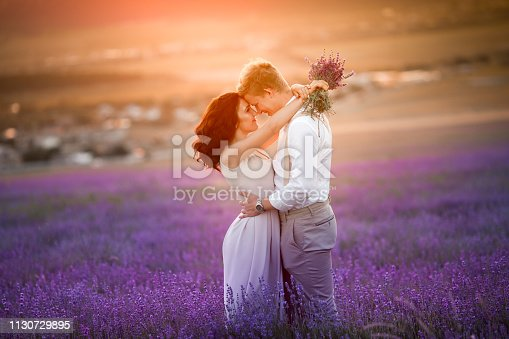 istock Romantic couple in an endless lavender field at sunset. blond Man and red-haired girl with a bouquet of flowers in love and hugs. French lavender fields 1130729895