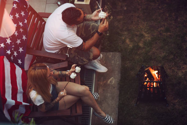 Romantic Couple In Backyard Romantic couple in backyard sitting by the fire and roasting marshmallow. american flag tattoos for men stock pictures, royalty-free photos & images