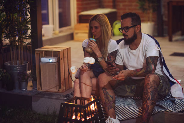 Romantic Couple In Backyard Romantic couple sitting in backyard and roasting marshmallow. Watching their photos on projection screen. american flag tattoos for men stock pictures, royalty-free photos & images