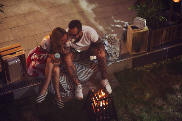 Romantic Couple In Backyard Romantic couple sitting in backyard, roasting and eating marshmallow. american flag tattoos for men stock pictures, royalty-free photos & images
