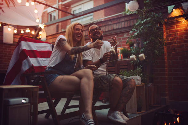 Romantic Couple In Backyard Romantic couple in backyard sitting by the fire and roasting marshmallow. Watching their photos on big screen. american flag tattoos for men stock pictures, royalty-free photos & images