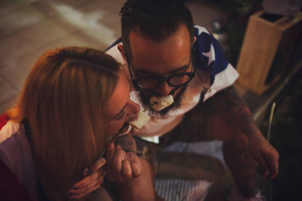 Romantic Couple In Backyard Romantic couple in backyard sitting by the fire and eating roasted marshmallow. american flag tattoos for men stock pictures, royalty-free photos & images