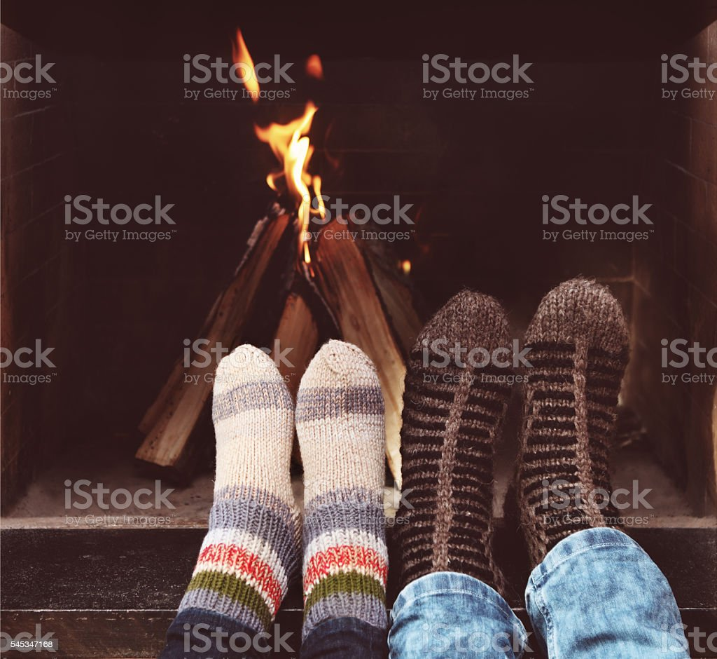 Romantic couple in front of fireplace stock photo