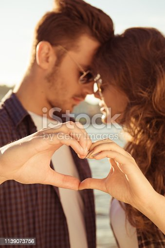 950598260 istock photo Romantic couple in love gesturing a heart with fingers at sunset 1139073756