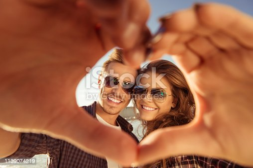 950598260 istock photo Romantic couple in love gesturing a heart with fingers 1139074219